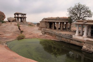 A green pond and temples on Hemakuta Hill in Hampi.