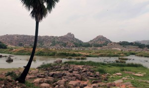 View of the Thungabgadra River with stone pillars still standing where an ancient bridge once crossed the river.