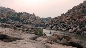 Ruins and boulders along the Thungabgadra River with a round boat being paddled by a local.