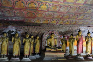 Buddha statues hanging out with each other inside of the cave temple.