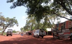 Safari vehicles stopped at a roadside souvenir shop.