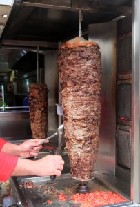 Chef cutting slices of shawarma.