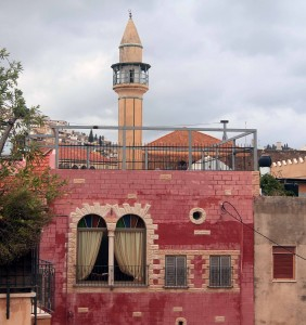 Colorful facade and a minaret behind it.