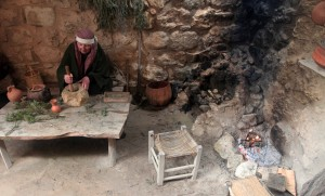 A woman grinding rosemary with a mortar and pestle.