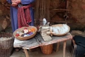 A woman creating yarn from sheep's wool.