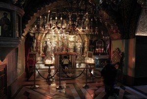 Altar of the Crucifixion with a woman praying under the altar.