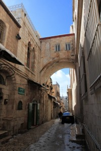 The Via Dolorosa outside of the Ecce Homo Convent with the largest of Hadrian's triple arch partially exposed and spanning the street.