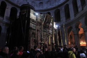 Priests and pilgrims at the Aedicule inside the Church of the Holy Sepulchre - the Fourteenth Station, Jesus is laid in His Tomb.