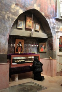 A woman is praying at a glass casket that holds the remains of a Romanian monk who died in 1960 AD.