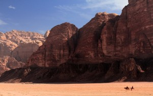 Four people, three camels, and a dog passing through Wadi Rum.