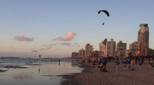 Two men power-paragliding above the beach in Tel Aviv.