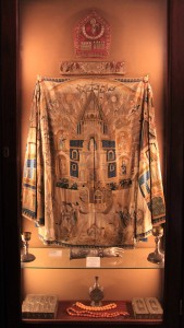 Priestly vestments on display in a case with a Right Hand Reliquary containing a relic of St. Sargis.