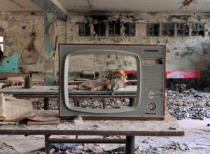 Front of a television set and a doll wearing a child's gas mask behind it.