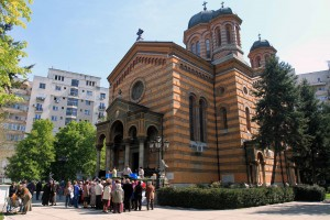 Lady Balasa Church in Bucharest with parishioners outside filling their plastic bottles with Holy Water.