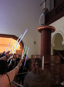 Visitors hold fluorescent light tubes up to an active Tesla Coil to illuminate them.