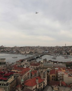 A seaplane flying over Galata Bridge and the Golden Horn.