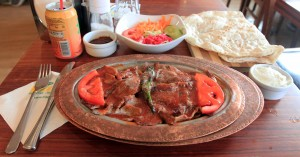 İskender kebap with a salad, bread, minced spices, and yogurt.
