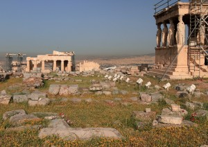 View of the Propylaea in the distance and the Porch of the Caryatids (part of the Erechtheion) on the right.