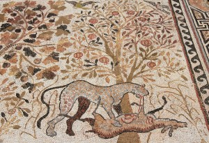 Mosaic of a deer having its intestines ripped out under a pomegranate tree.