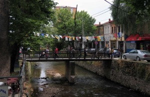 "Bridge over the Dragor River (with ""Welcome to Bitola"" flags that look an awful lot like Tibetan Buddhist flags when viewed from a distance)."