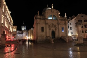 """St. Blaise Church with Dubrovnik Cathedral (also known as the """"Cathedral of the Assumption of the Virgin Mary"""") in the background, at night."""