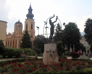 """Multicultural Man Builds the World"" statue with the Serbian Orthodox Cathedral in the background."