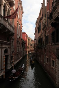 A narrow canal with gondolas going both ways.