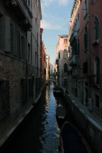 A narrow stream of sky reflected on a canal in Venice.