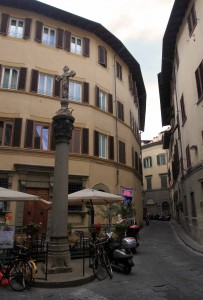 Street in Florence with a column topped with a Cross.