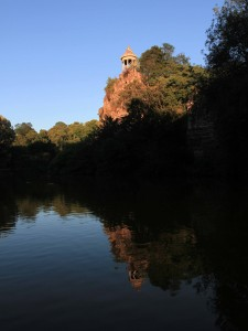An artificial lake inside the park with the Temple de la Sibylle on top of a cliff.