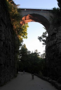 "A path in the Parc des Buttes-Chaumont with the ""suicide bridge"" overhead."