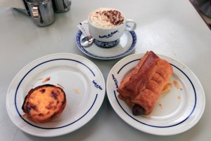 My afternoon snack of a Pastel de Belem, a puff pastry sausage roll, and a cappuccino.