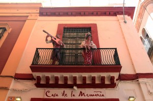 A balcony in Seville with festive figures.