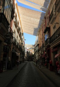 Street in Seville with shade covers overhead.
