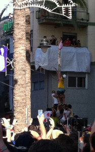 People try to reach the large ham hanging at the top of the tall, greased wooden pole located in the center of the La Tomatina action in Buňol.