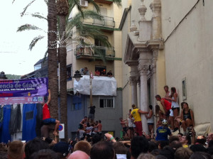 Watching people trying to climb up the ham pole and a man imitating them by trying to climb up a palm tree while waiting for the 70th La Tomatina to begin.