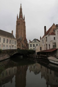 Canal with the bell tower of the Church of Our Lady in Bruges in the background.