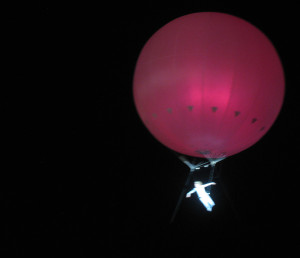 A woman attached to a giant balloon, floating over the crowds at the conclusion of Berlin Lollapalooza.