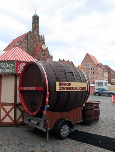 A giant keg parked in the Hauptmarkt alongside a food stall.