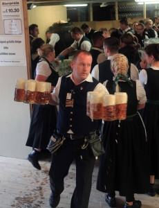 A server carrying 12 liters of Paulaner beer to some thirsty patrons.