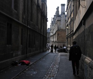 Street in the University of Oxford with a homeless man sleeping on the sidewalk.