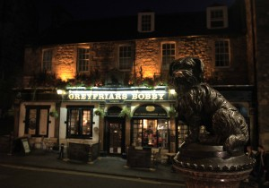 Greyfriars Bobby statue and pub at night.