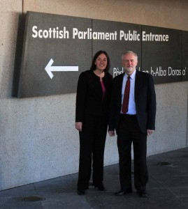 Jeremy Corbyn, the leader of the Labour Party in the United Kingdom, and an unidentified lady standing outside of the entrance to the Scottish Parliament building.
