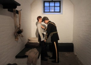 A cell inside the military prison at Edinburgh Castle; this mock-up shows Private John Tool (charged with desertion) being examined by a member of the army's Medical Staff Corps.