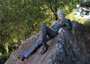 Statue of Oscar Wilde lounging on a boulder in Merrion Square gardens.