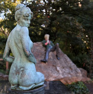 Statue of a pregnant woman kneeling with Oscar Wilde in the background.