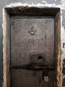 A bolted and locked prison cell door.