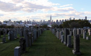 More tombstones at the First Calvary Cemetery, with the Empire State Building in the distance.