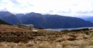 View of Luxmore Hut, the South Fiord of Lake Te Anau, and the mountains on the other side.