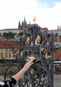 A woman touching a small bronze sculpture that marks the spot where St. John Nepomuk was thrown off Charles Bridge in 1393 AD.